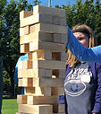 This is a picture of gaint jenga with a white female in the background.