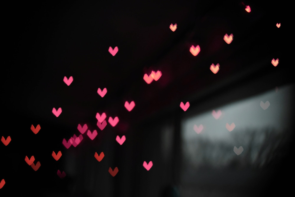 floating pink hearts on a black background