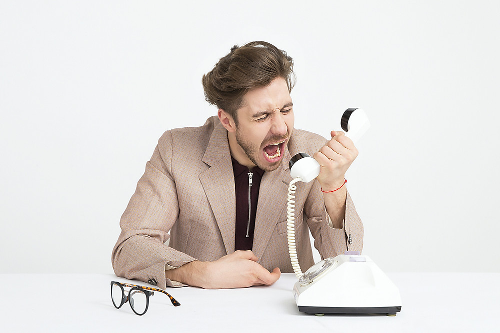 man yelling into a telephone