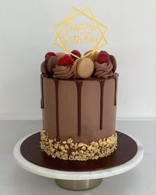 Chocolate drip cake, macarons and raspberries
