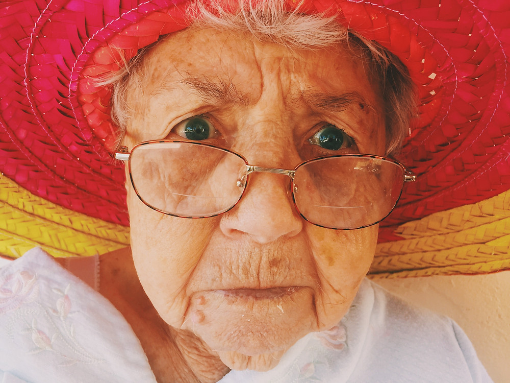 Close up photo of an older woman with a red straw hat and glasses
