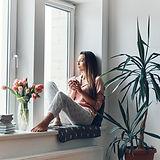 Woman sitting on a window sill
