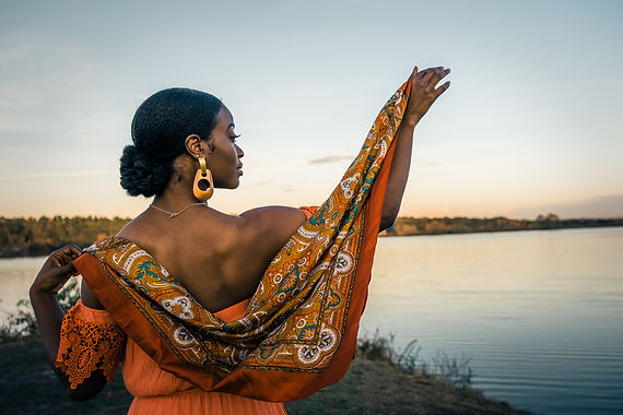 Magic hour photograph of glamorous woman with orange scarf