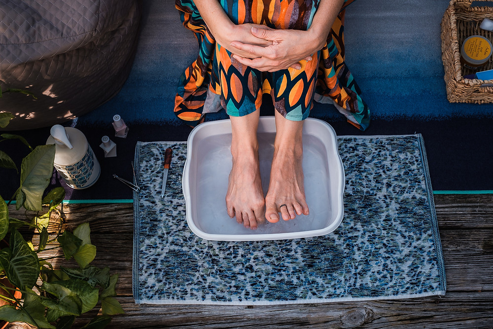 Woman soaking feet in a foot bath in a cozy deck scene, getting ready for a self care DIY manicure and pedicure  for personal brand photography.