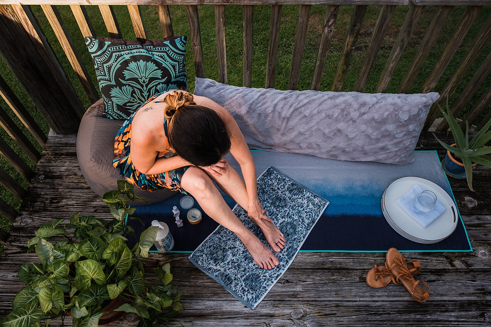 Woman in a comfortable deck scene moisturizing feet and legs. Self care DIY manicure and Pedicure for personal brand photography.