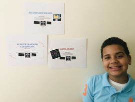 Student with three certificates on wall
