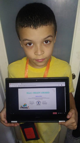 Student holding certificate on computer