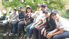 Students at the park smiling at the camera