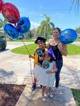 Student with graduation balloons and family