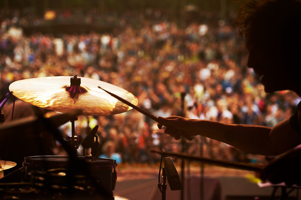 Drummer on stage with huge crowd in audience