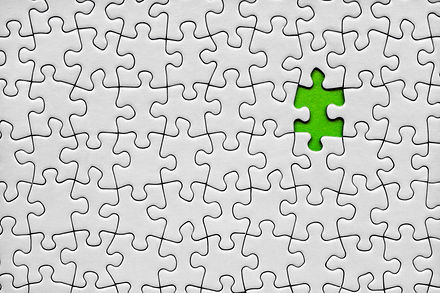 Jigsaw puzzle with one green piece missing.jpg