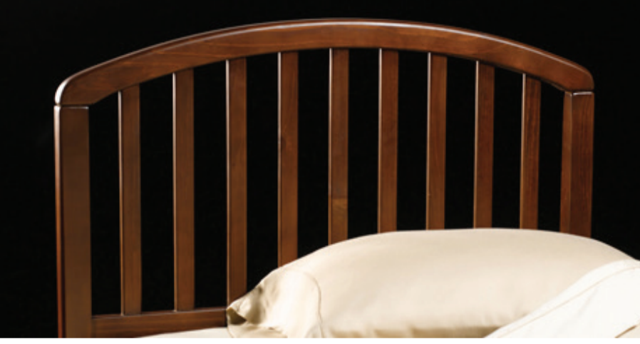 pine wood slatted headboard with curved top against black background with white pillow