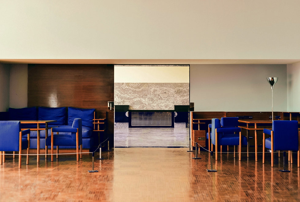 hotel lobby with wooden tables and blue seats on either side of an open door leading to front desk
