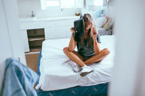professional fashion photographer sunshine coast: photoshoot of female modeling clothing on bed