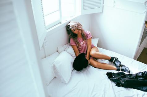 professional fashion photographer sunshine coast: photoshoot of female model posing on bed