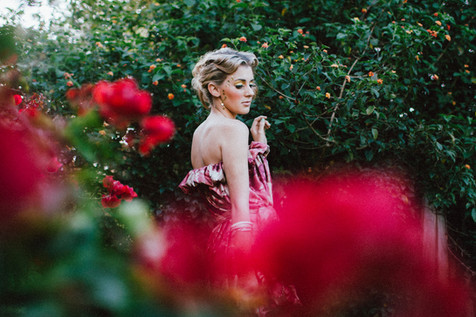 professional fashion photographer brisbane: photoshoot of female modeling a floral dress posing between pink flowers