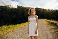 professional model photography brisbane: portfolio photoshoot of female modeling white dress on dirt road