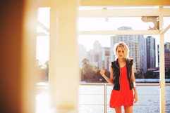 professional model photography brisbane: portfolio photoshoot of female wearing red dress by city river