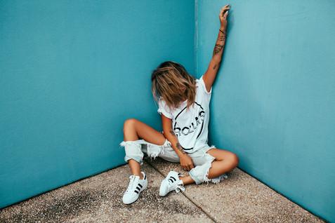 professional fashion photographer sunshine coast: photoshoot of female model posing in corner of blue wall