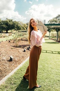 professional fashion photographer brisbane: lifestyle photoshoot of female modeling purse in garden