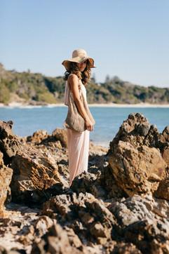 professional fashion photographer byron bay: photoshoot of female model posing at rocky beach