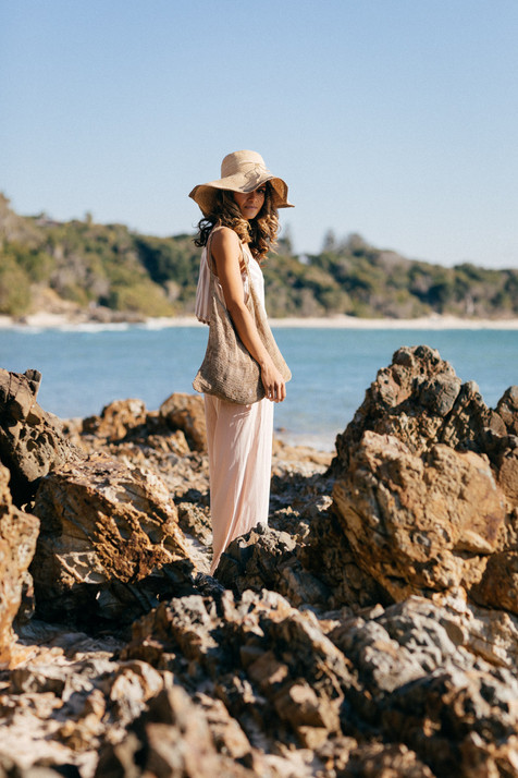 professional fashion photographer byron bay: photoshoot of bruntette female model posing between rocks at the beach with bag and hat