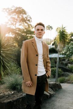 professional model photography brisbane: backlit portfolio photoshoot of male wearing trench coat