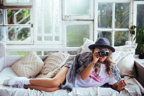 professional fashion photographer sunshine coast: photoshoot of female model posing with camera on day bed infront of windows