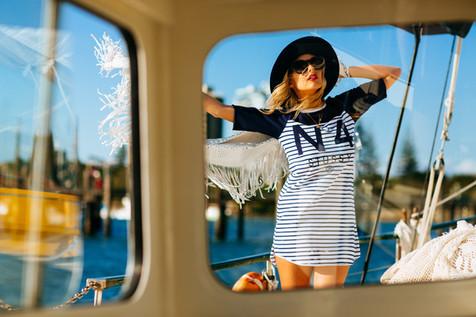 professional fashion photographer sunshine coast: photoshoot of female model on boat wearing nautical clothing