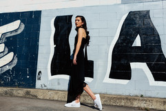 professional fashion photographer brisbane: photoshoot of female modeling black dress infront of graffiti