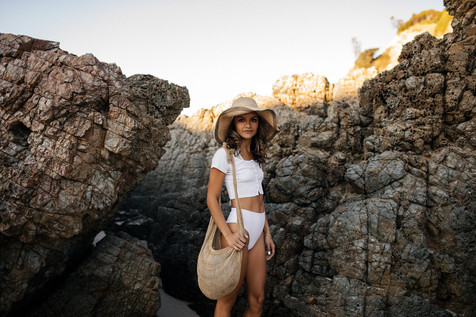 professional fashion photographer gold coast: photoshoot of female posing in beach outfit between rocks