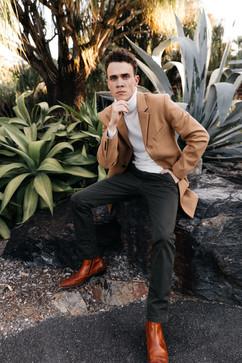professional model photography brisbane: modeling portfolio headshot of male model posing on rock in coat, long pants and leather shoes