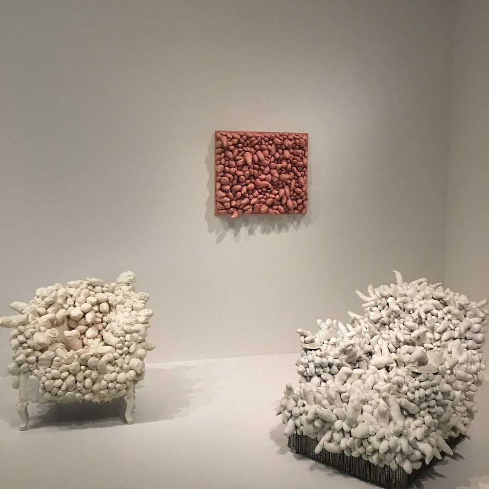 2 white Kusama couch sculptures and a sculpture wall piece