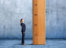 Businesswoman-Looks-Up-At-Large-Wooden-R