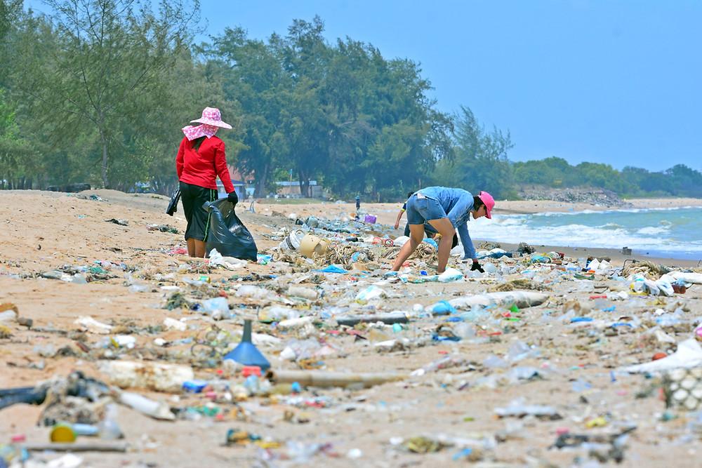 Women cleaning up a littered beach