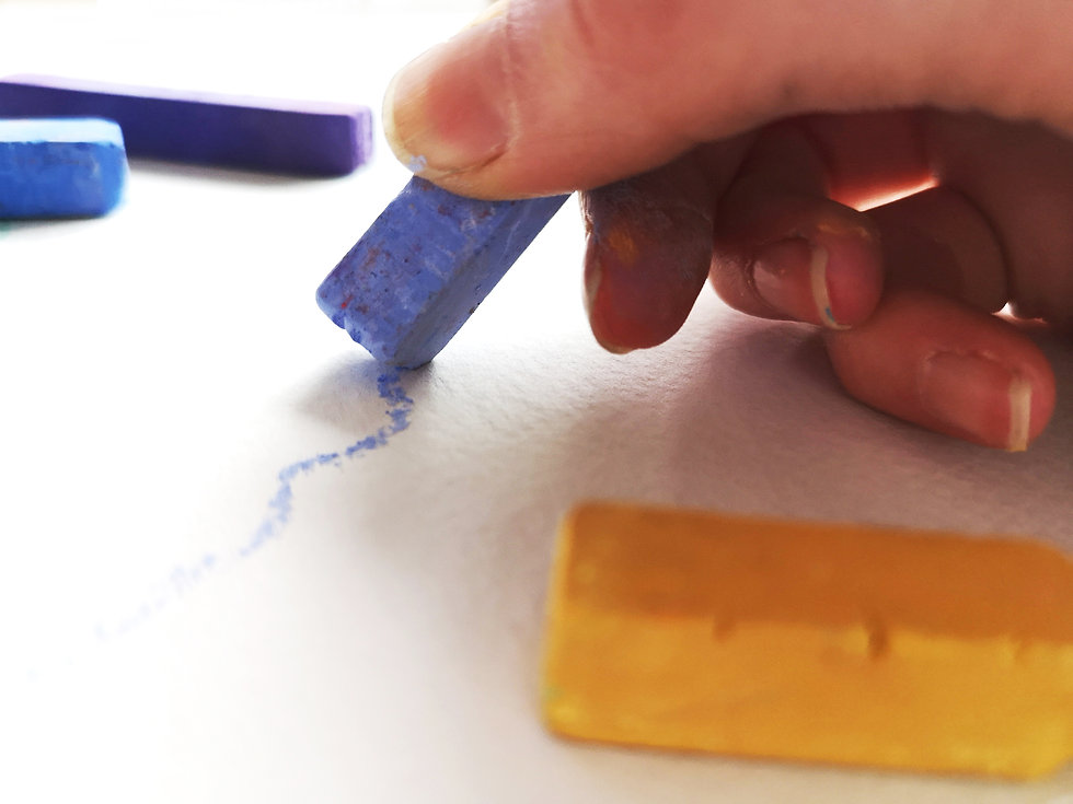 artist hand drawing with pastels on paper with purple and yellow