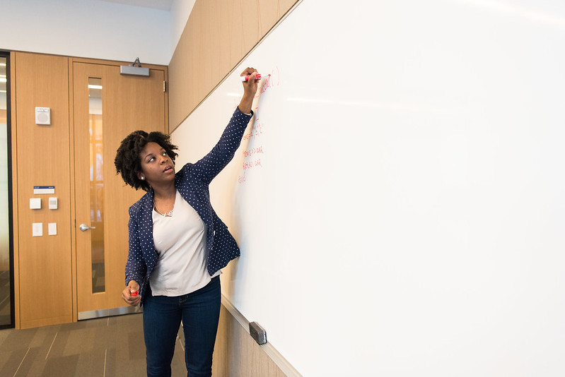Woman standing by a whiteboard writing down notes