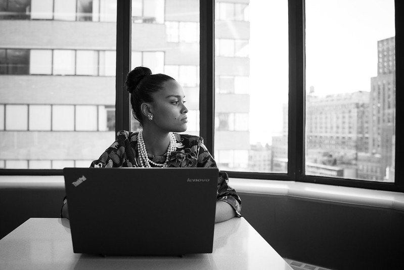 Woman on a laptop looking out a window