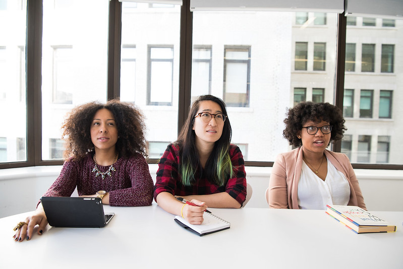 Three women at a conference table listening to a presentation