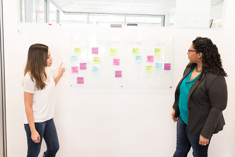 Two women conducting a brainstorming exercise on a whiteboard.