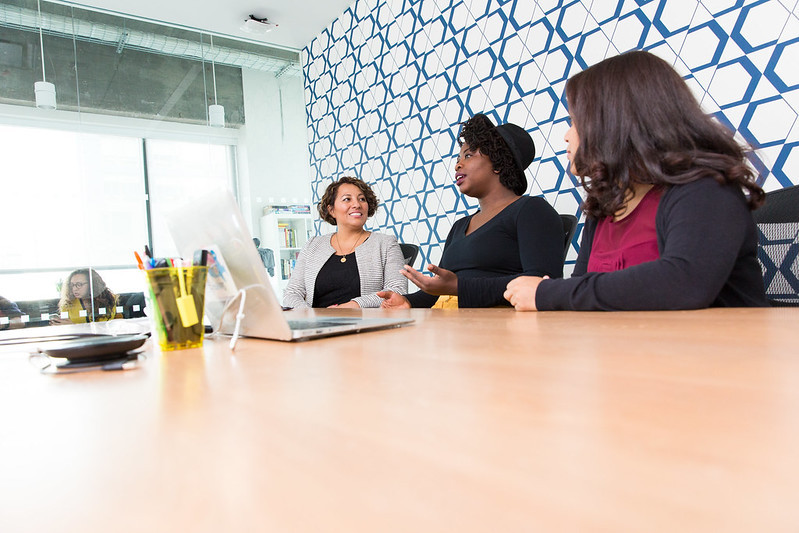 Three women conversing around a conference table