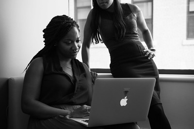 A woman on a laptop and another woman standing over her and looking at the laptop screen