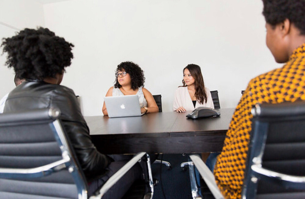 Women sitting at a conference room table with a laptop in the middle