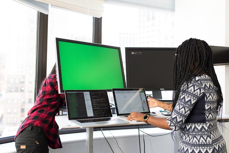 Two women setting up computer monitors