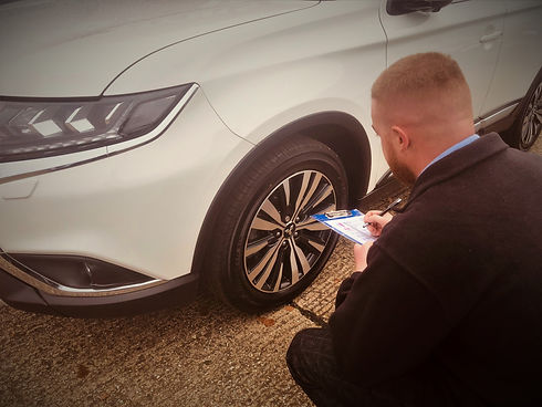 Man inspects car with clipboard
