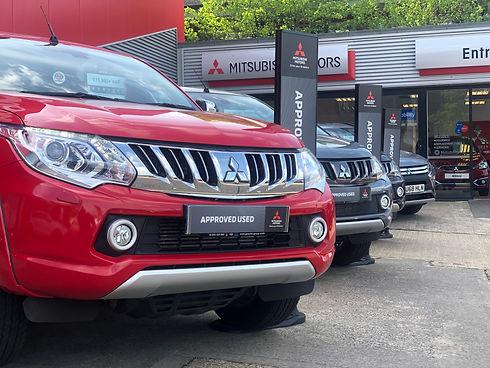 Row of Mitsubishi vehicles outside showroom