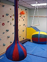 This is a picture of a sensorimotor gym containing a rock wall and swings at The Kids' Communication Center, a private practice in Tenleytown, DC that provides speech-language therapy to kids or children.