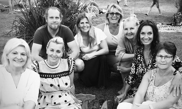 Das Team von Sommerhaus Decorationen sitzt zusammen auf einer Wiese