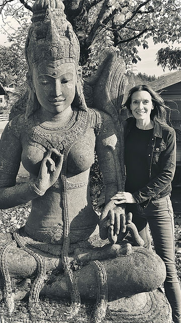 Barbara Seiler lehnt neben der indonesischen Steinfigur Dewi Sri