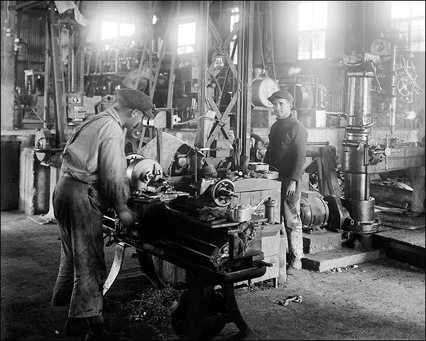 Bir işçi makine üzerinde çalışırken diğer işçi boşta bekliyor.